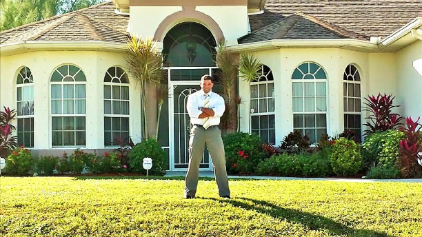 Proud homeowner in front of his property