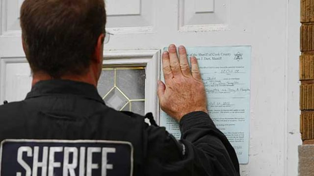 Sheriff Posting Eviction Notice in Fron Door