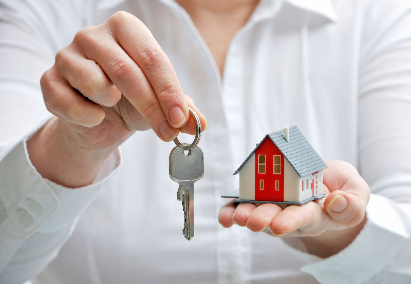 Woman giving model house and keys.